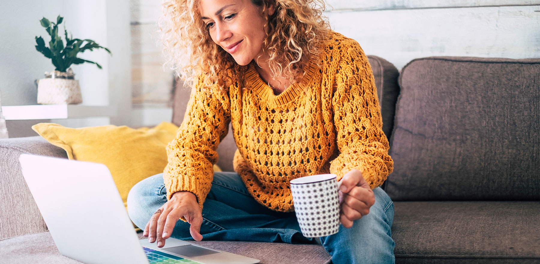 Woman sitting on a couch, holding a coffee mug, and checking her laptop
