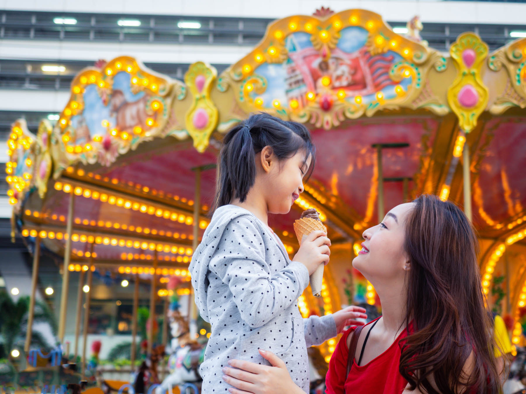 happy asia mother and daughter have fun in amusement carnival park with farris wheel and carousel background