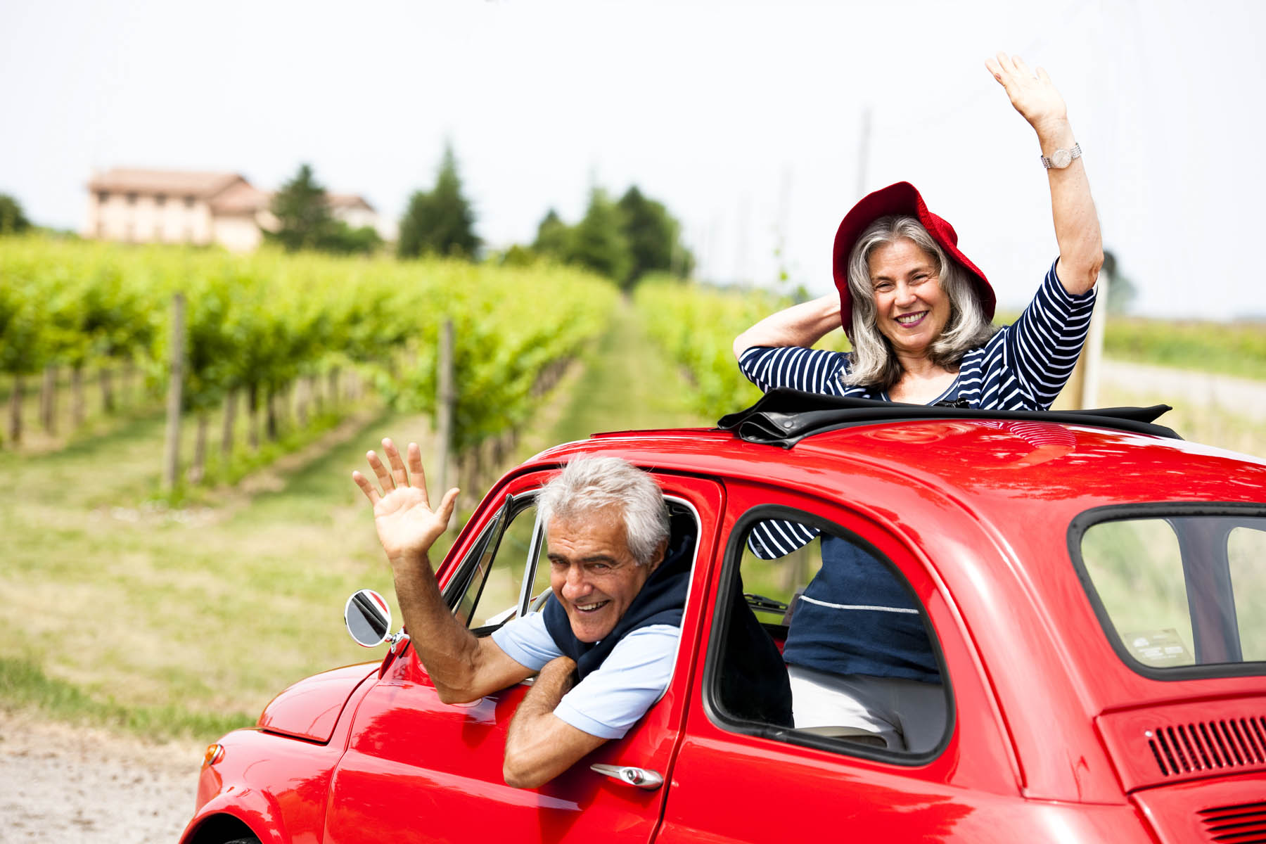 Senior happy couple driving vintage car